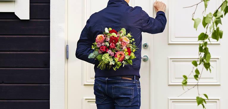 Mann hält orangenes Blumenbouquet hinter seinem Rücken und kopft an Haustür