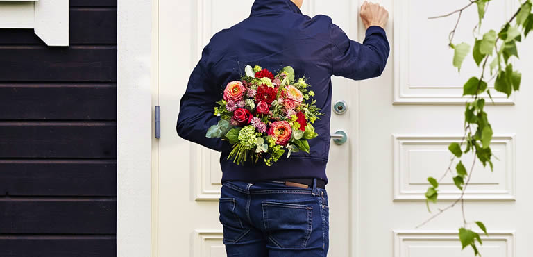 Man holding orange bouquet behind his back and knocking on house door